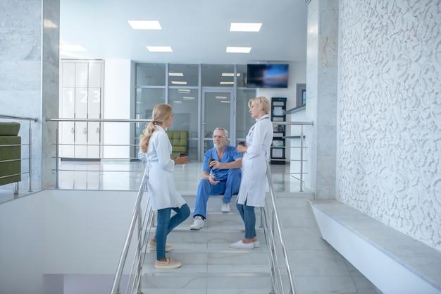 Pausa caffè. team di operatori sanitari che riposa, bevendo caffè sulle scale
