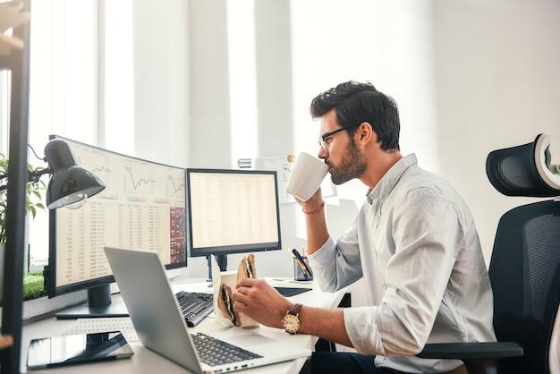 Pausa caffè giovane uomo d'affari o commerciante barbuto sta bevendo un caffè e mangiando un panino