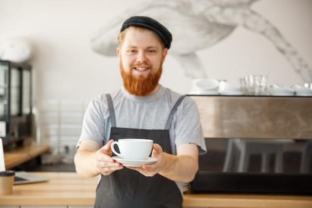 Caffè concetto di business azienda - ritratto di giovane barbuto felice giovane barbuto caucasico in grembiule con fiduciosi cercando di servire il caffè caldo al cliente nel banco del caffè.