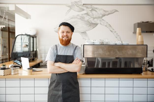 Caffè business proprietario concetto - ritratto di felice giovane barbuto barista caucasico in grembiule con fiducioso cercando e sorridente alla fotocamera nel banco del caffè.