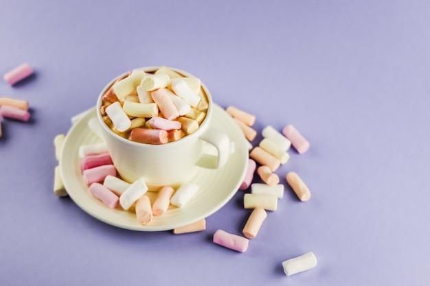 Bevanda al caffè o al cacao con soffici dolci marshmallow su un viola minimalista