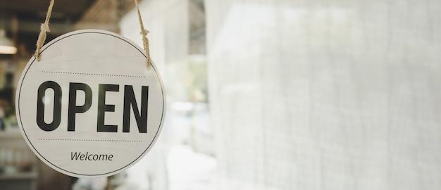Testo del negozio di caffè caffè sul cartello vintage appeso alla porta di vetro nel moderno negozio di caffè