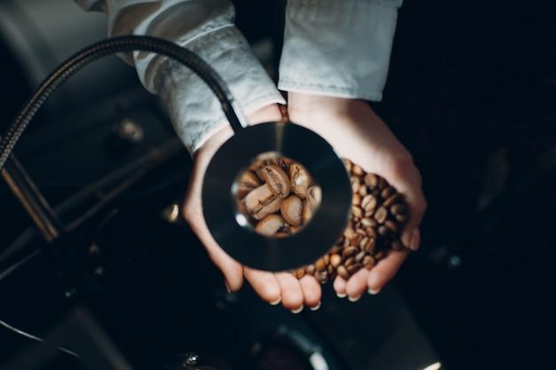 Raffreddamento del caffè nella macchina per la torrefazione durante il processo di torrefazione del caffè giovane lavoratrice barista che mescola e tiene i chicchi di caffè in mano alla lente d'ingrandimento