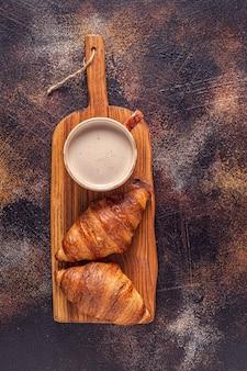 Caffè e croissant su fondo di pietra. colazione francese. vista dall'alto con copia spazio.