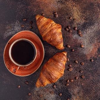 Caffè e croissant su sfondo di pietra
