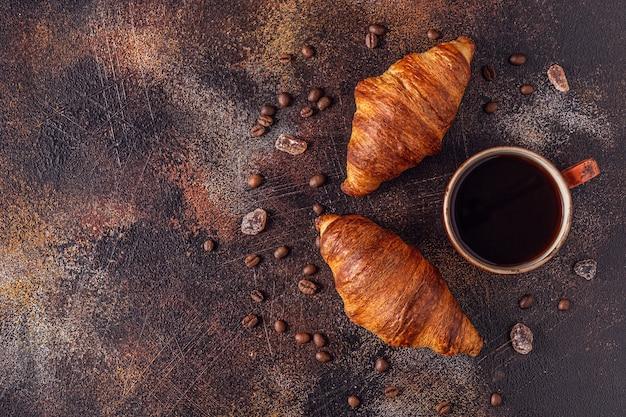 Caffè e croissant su pietra. colazione francese. vista dall'alto con copia spazio.