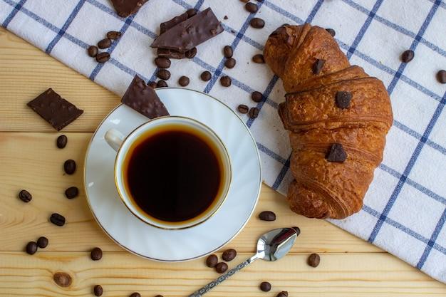 Caffè e croissant su uno sfondo di legno. la vista dall'alto. chicco di caffe