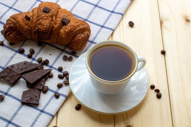 Caffè e croissant su uno sfondo di legno. la vista dall'alto. chicchi di caffè e cioccolato