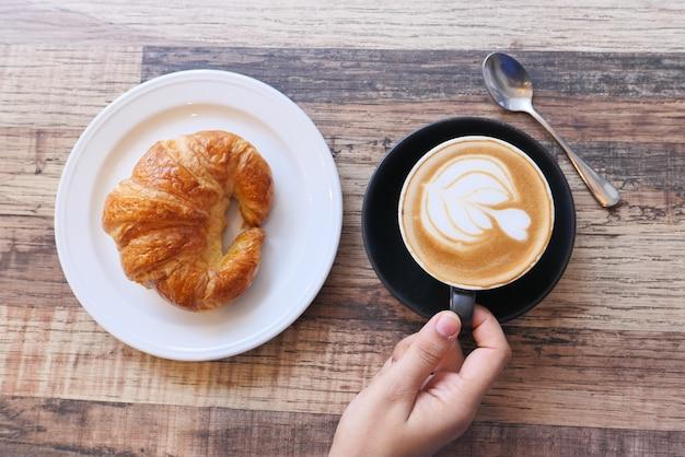 Caffè e croissant sul tavolo in legno vista dall'alto