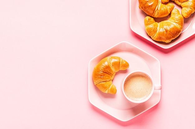 Caffè e croissant per colazione su uno sfondo rosa, vista dall'alto, piatto laico.