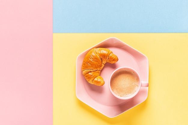 Caffè e croissant su uno sfondo luminoso e alla moda, vista dall'alto, piatto laici.
