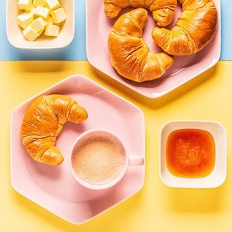 Caffè e croissant su uno sfondo luminoso e alla moda