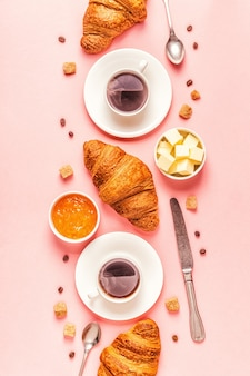 Caffè e croissant su sfondo pastello, vista dall'alto.