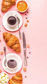 Caffè e croissant su pastello, vista dall'alto.