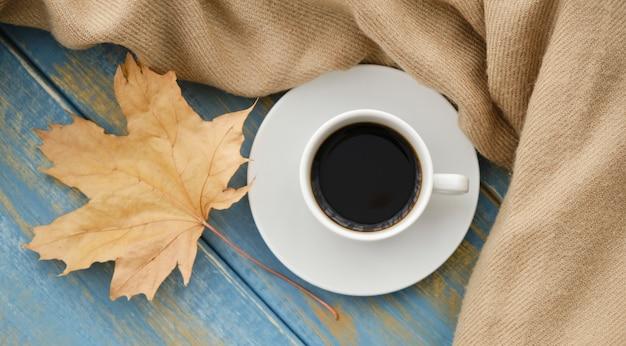 Tazza di caffè sulle foglie autunnali e sullo sfondo della superficie in legno Foto Premium