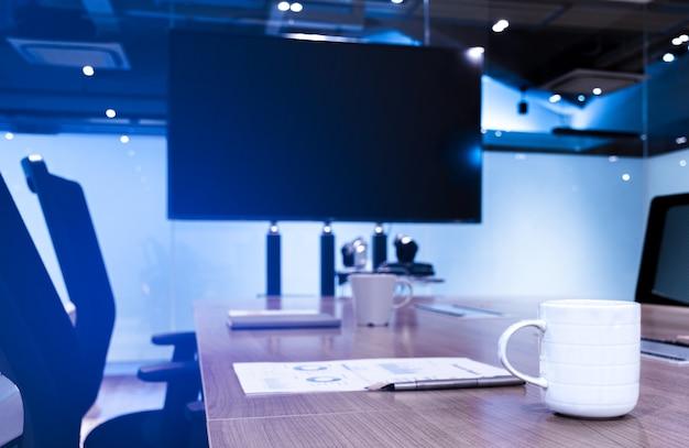 Tazza da caffè penna a sfera e documenti sul tavolo con sfondo televisivo a schermo vuoto in riunione