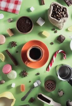 Tazza di caffè e fagioli su sfondo di carta verde, vista dall'alto