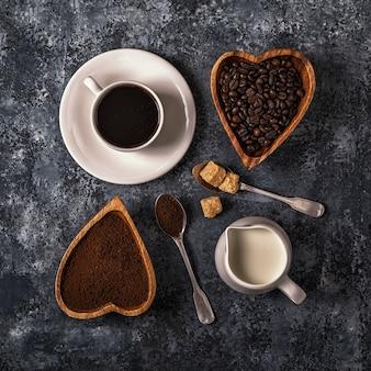 Tazza di caffè, fagioli e polvere macinata su fondo di pietra