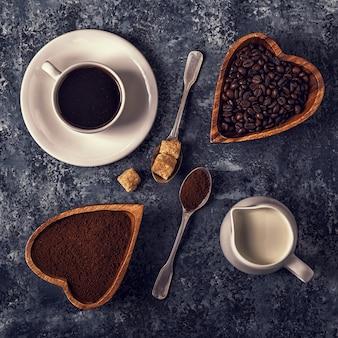 Tazza di caffè, fagioli e polvere macinata sul tavolo di pietra.