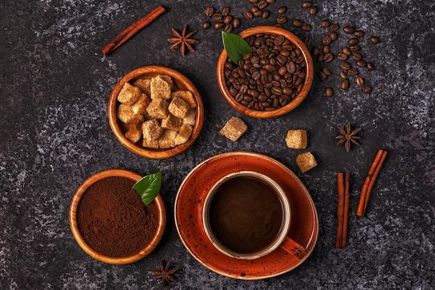 Tazza di caffè, fagioli, polvere macinata e zucchero su fondo di pietra