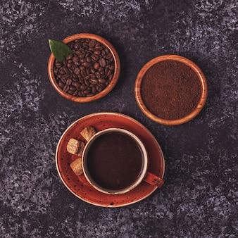 Tazza di caffè, fagioli, polvere macinata e zucchero su pietra