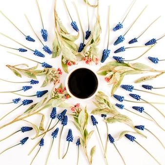 Tazza di caffè, bellissimi fiori di muscari blu e fiori di campo su sfondo bianco. disposizione piatta, vista dall'alto