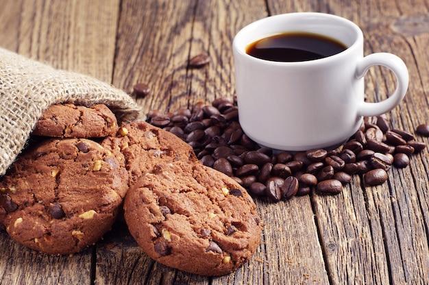 Tazza di caffè e biscotti al cioccolato con noci sulla vecchia tavola di legno
