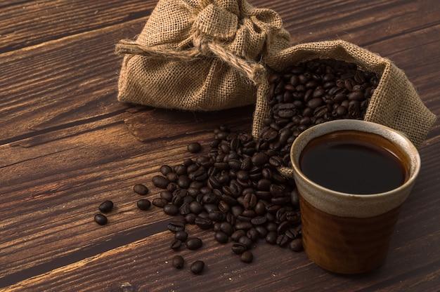 Tazza di caffè e chicchi di caffè sulla tavola di legno