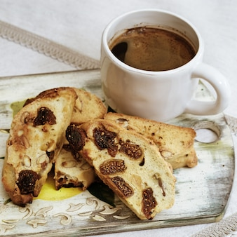 Biscotti della tazza e dei biscotti di caffè sul bordo di legno.