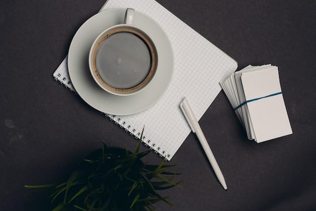 Primo piano da tavolino dell'ufficio della penna del biglietto da visita della tazza di caffè