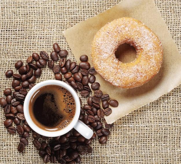 Tazza di caffè e ciambella con zucchero su uno sfondo di tela vista dall'alto