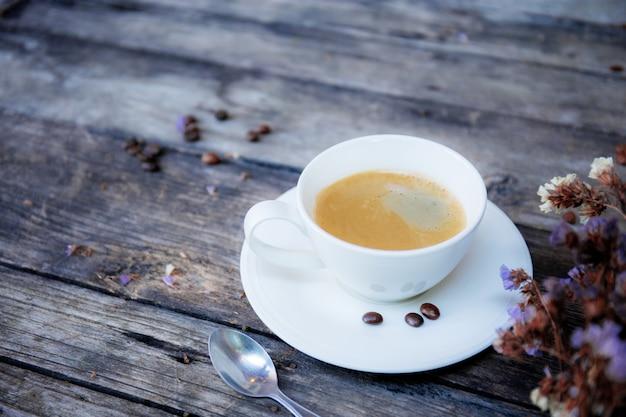 Tazza di caffè e fiori sul tavolo.