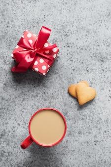 Tazza di caffè e regalo, biscotti fatti in casa del cuore sul tavolo grigio. biglietto di auguri di san valentino. vista dall'alto. formato verticale.