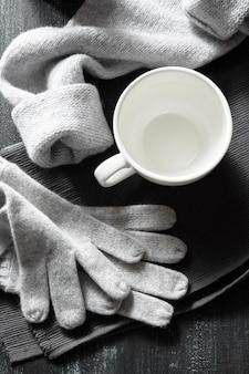 Tazza di caffè e cose lavorate a maglia fatte a mano su una superficie nera
