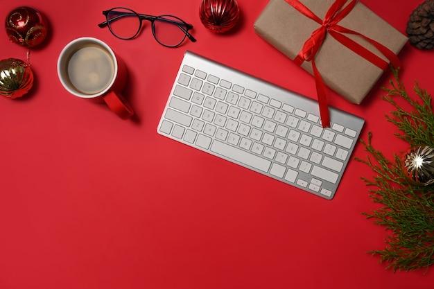 Tazza di caffè, tastiera e scatole regalo su sfondo rosso.