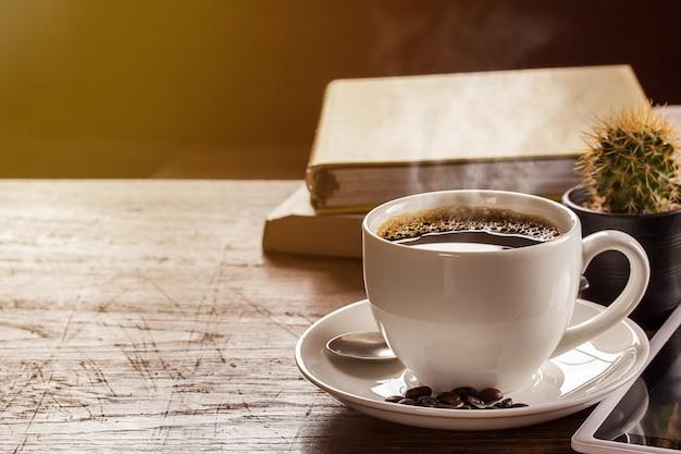 Tazza di caffè e taccuino sulla tavola di legno
