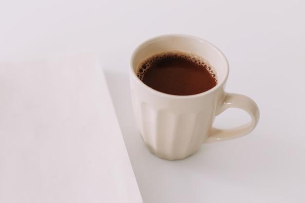 Una tazza di caffè e un taccuino. colazione di lavoro su sfondo bianco. vista piana, vista dall'alto, desktop da ufficio