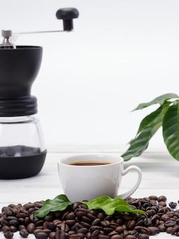 Tazza di caffè sul mucchio di fagioli.