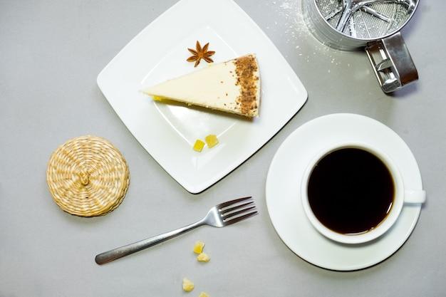 Tazza di caffè e un piatto con i biscotti su uno sfondo.