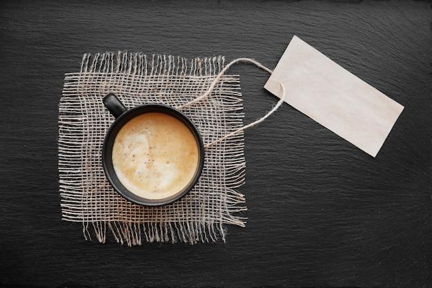 Tazza di caffè su tela rustica e carta di carta bianca