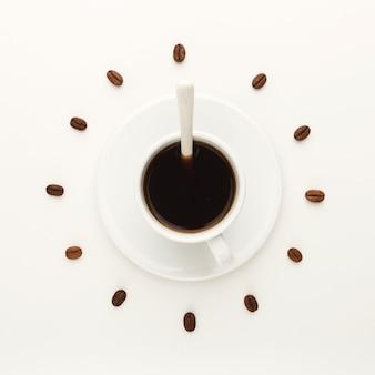 Tazza da caffè sul piattino e fagioli tostati disposti come quadrante su sfondo bianco isolato, vista dall'alto. simbolo dell'ora del caffè. concetto di energia e ristoro, spazio di copia