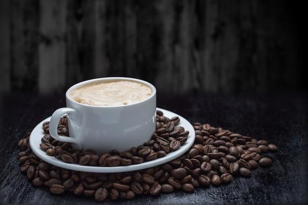 Tazza da caffè e piattino su un tavolo di legno. sfondo scuro.