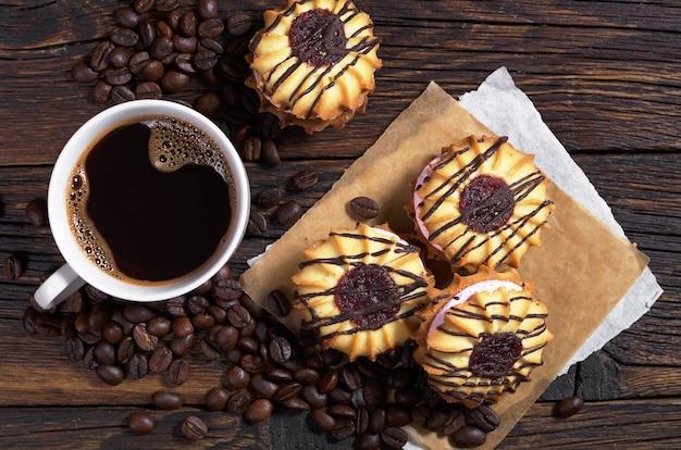 Tazza di caffè e biscotti di pasta frolla con crema e cioccolato sul tavolo di legno scuro, vista dall'alto