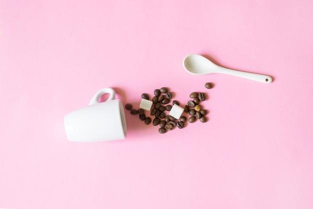 Tazza di caffè, cucchiaio e fagioli con zucchero su uno sfondo rosa, concetto di mattina.
