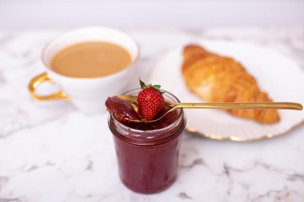 Tazza di caffè e croissant dolce con marmellata di fragole fresca sul tavolo bianco