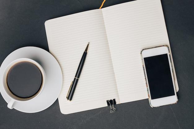 Tazza di caffè sul blocco note della tabella con una tecnologia del telefono della penna. foto di alta qualità