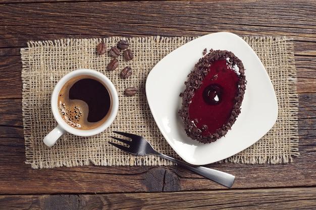 Tazza di caffè e gustosa torta al cioccolato con gelatina di ciliegie sul tavolo di legno scuro, vista dall'alto