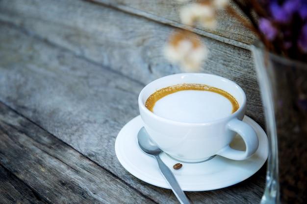 Tazza di caffè e vaso sul tavolo.