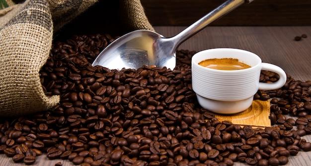 Tazza da caffè con sacco di tela di fagioli arrostiti su tavola rustica