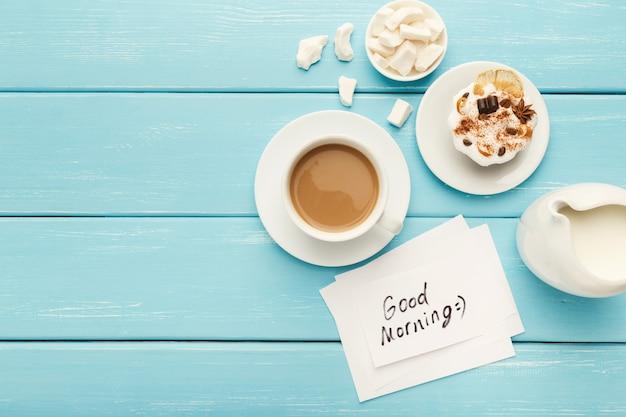 Tazza di caffè con torta e nota buongiorno sul tavolo rustico blu dall'alto. vista dall'alto su una colazione accogliente e gustosa, copia spazio